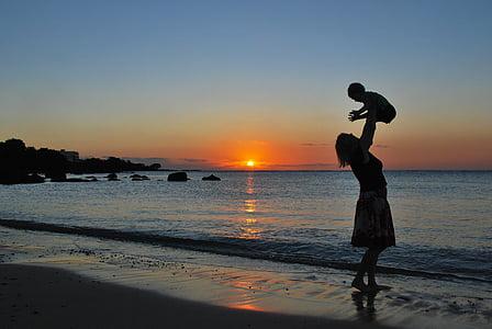 woman carrying baby near seashore