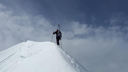 man climbing on top of snow mountain