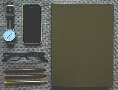 green iPhone 5c, eyeglasses with black frame, black notebook, watch, and three ballpoint pens