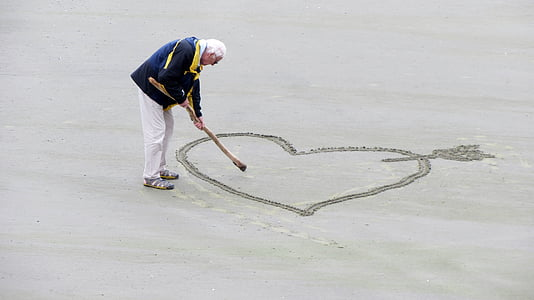 man sketching heart with arrow on sand \