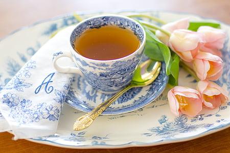 teacup on saucer beside pink flowers