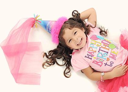 girl wearing pink Happy Birthday-printed top lying photo