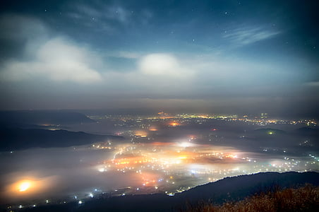 aerial photography of city light near fogs and mountain