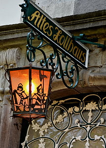 green and yellow steel Altes Lollhaus signage with hanging lamp