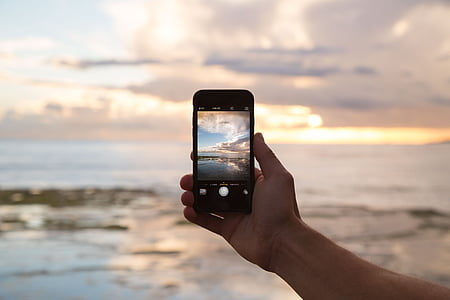 person taking photo of the ocean
