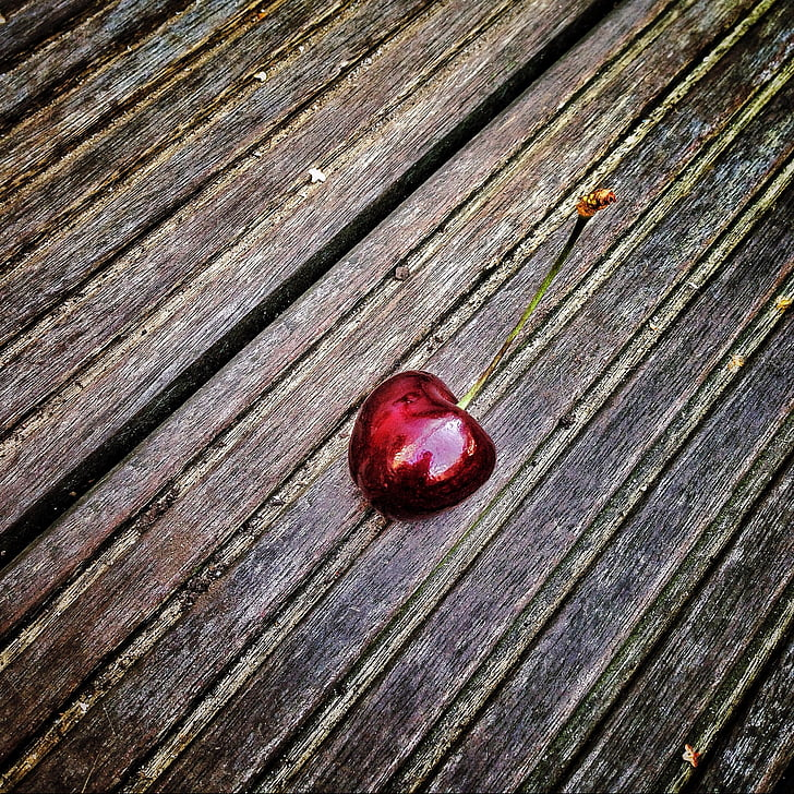 red cherry on black and brown surface