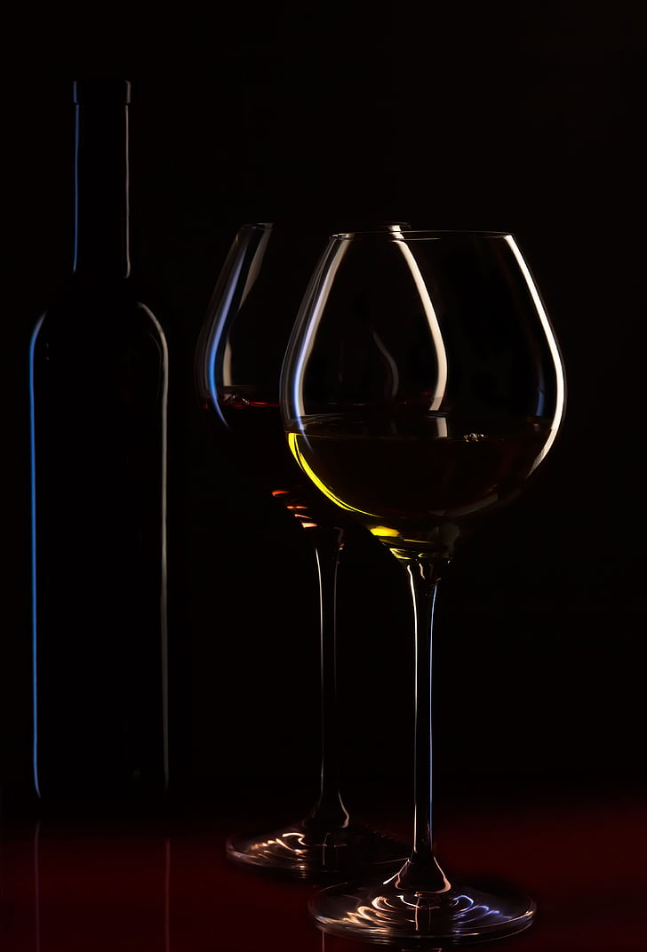 clear glass wine glasses with wine and bottle