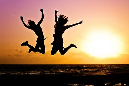 jump shot silhouette of two women during golden time