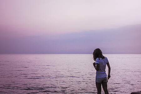 landscape photo of woman standing in front of sea
