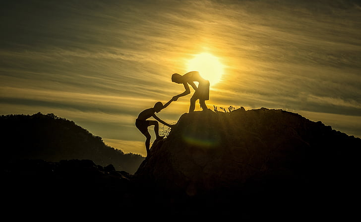 silhouette of man helping another man to climb on cliff during golden hour