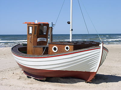 white and brown boat on gray sand