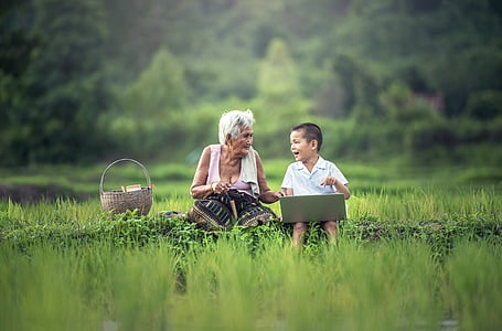 boy with laptop sitting beside white haired woman on green field