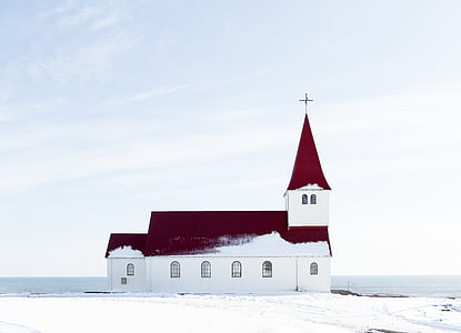 red and white chapel near body of water