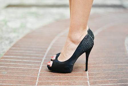 woman in black peep-toe platform pumps stepping on brown pavement