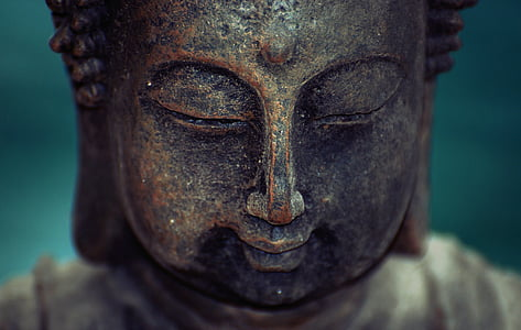 brass-colored buddha face statue
