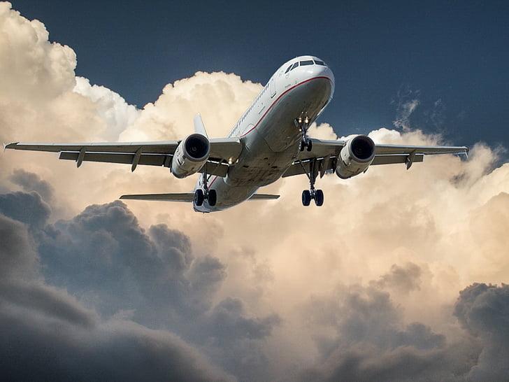 white passenger plane flying mid air during daytime
