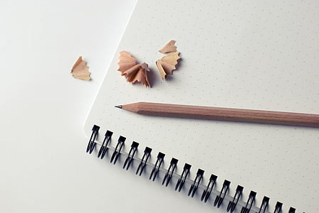 brown pencil on white spiral notebook