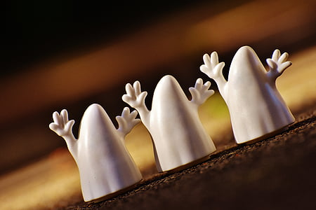 shallow focus photo of three white ghost figurines