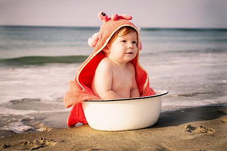 baby sitting on white basin on seashore
